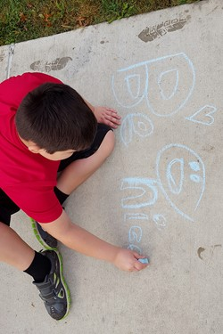 Student uses chalk to draw on the sidewalk