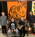 four kids in front of tiger mural