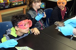 children wearing rubber gloves in classroom