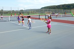 Elementary students learn to volley a ball during the tennis clinic.