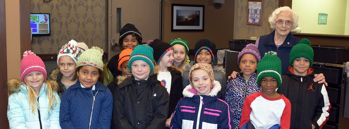 CFJ students with their new hats knitted by Catherine Lewis at Vestal Park.
