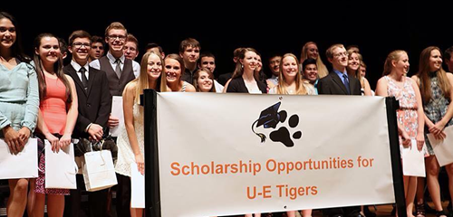 people holding up sign for scholarships